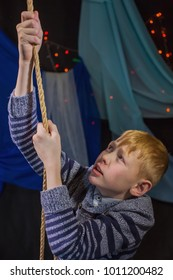 A red-haired boy climbs the rope up