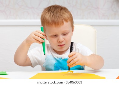 red-haired boy drawing on paper