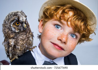 red-haired boy with freckles and his feathered friend owl, kid and owl, boy with red hair and bird of prey on the shoulder are best friends, happy freckles face