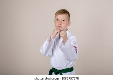 Red-haired boy with a green belt in a kimono in a photo studio. An athlete achieving success in taekwondo.