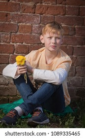 A red-haired boy is holding a bouquet of dandelions