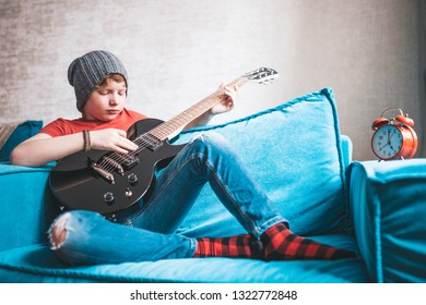 Red-haired boy in jeans and a cap sitting on the couch performs an exercise on playing a black electric guitar - rock and rock-roll style