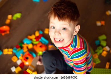 red-haired boy in a multi-colored jacket holds plays in the constructor lego