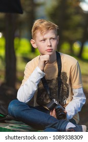 The red-haired boy sitting with a camera
