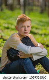 The red-haired boy sitting on the grass