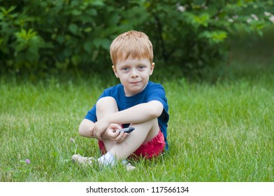 Red-haired boy sitting on the grass