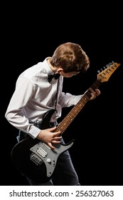 The red-haired boy in a white shirt with an electric guitar on a black background