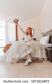 The red-haired bride is sitting on the bed. Her feet are stretched out in front of her and she is wearing sneakers. In the hand a bouquet of red strawberries. The hand with the bouquet is raised up.