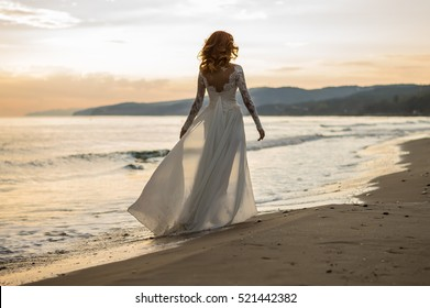 The red-haired bride. Wedding. Sea. Sandy beach. Sunset.