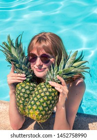 Red-haired Caucasian girl, poses by the pool with two pineapples