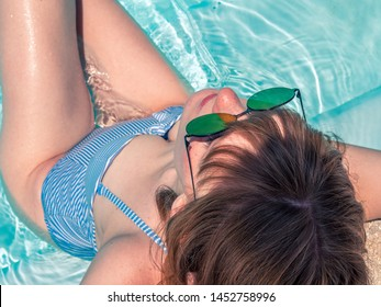 Red-haired Caucasian girl, sunbathing in the pool in a blue bathing suit