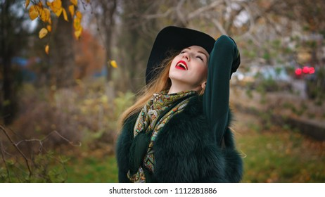 Red-haired girl in autumn park. She is wearing shorts and gloves and wide-brimmed hat. Woman is enjoying good weather.