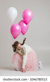 Red-haired girl with balloons  ties up shoelaces on sneakers on cyclorama