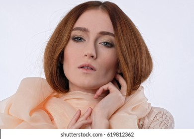 Red-haired girl in a big translucent scarf on white background. She lifted her hair by hands, mouth open, tender sight. Close-up shot. Warm colors