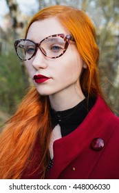 Red-haired girl with blue eyes and pale skin in a red coat. Woman in leopard glasses looking away. Portrait profile, ladybug. Red button. Red lips.