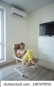 A red-haired girl in bright clothes and barefoot sits in a chair with a phone in her hands. A young woman sits in a bright room and is cooled on a hot day using an air conditioner.