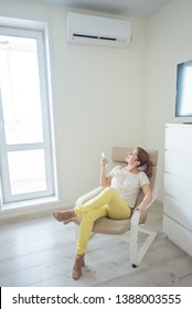 A red-haired girl in bright clothes and shoes  sits in an armchair with a remote control from the air conditioner. A young woman sits in a bright room and is cooled on a hot day using an air condition