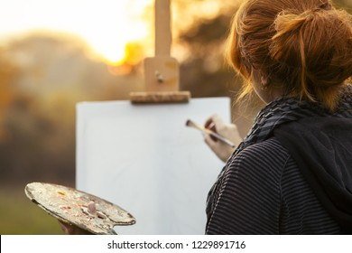 red-haired girl with a bun painting a picture on an easel in nature, a young woman involved in creativity and enjoying beautiful landscape at sunset , concept of seasons and hobby