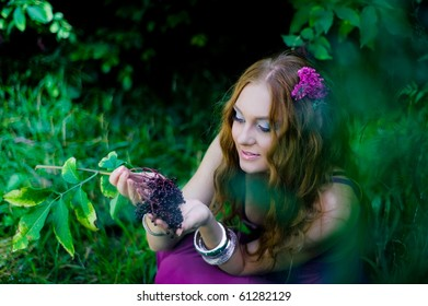 red-haired girl collecting berries in wood
