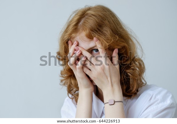 A red-haired girl with curls in embarrassment covers her face with her hands and looks through her fingers. Social phobia of the younger generation.