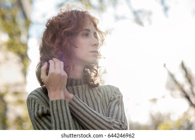 A red-haired girl with curls stands in the park and looks sadly away.