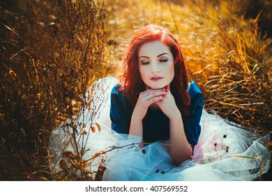 Red-haired girl in the field. Portrait