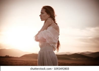 red-haired girl in a field of wheat in a white dress smiles a lovely smile , a perfect picture for advertising in the style lifestyle. beautiful cinematographic picture at sunset