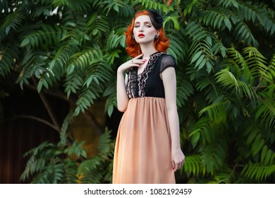 Red-haired girl in a free flying dress and retro hairstyle against a summer park background.