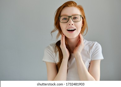 A red-haired girl with glasses stands on a gray background and happily looks into the camera, smoothing her hair.