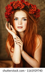 red-haired girl with gorgeous long hair and blue eyes in a wreath of Rowan on her head