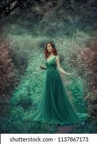 Red-haired girl in a green, emerald, luxurious dress in the floor, with a long train. The princess walks in a fairy forest. Simple and elegant hair in large waves. Artistic retouching