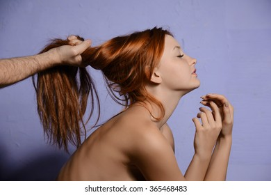 red-haired girl holding her hair male hand on a blue background