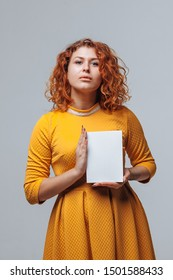Red-haired girl holding a white book on a light gray background.