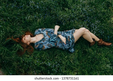 red-haired girl lying in the grass on a spring meadow