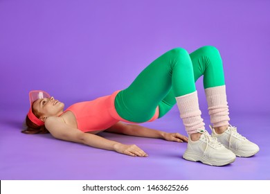 red-haired girl making hip raise, known well glute bridge to work out glutes and legs muscles, lying on floor, both legs knees bent, feet on ground, wears pink leotard, tight leggins and sport shoes