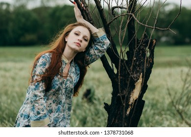 red-haired girl on a spring meadow
