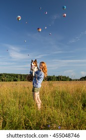 red-haired girl outdoors in a field holding his red-haired dog breed border collie, flying balloons in the sky, she was happy