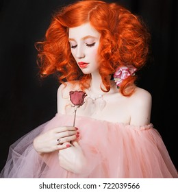 Red-haired girl with pale skin with a rose in hands on a black background. Beautiful beauty image with gentle makeup