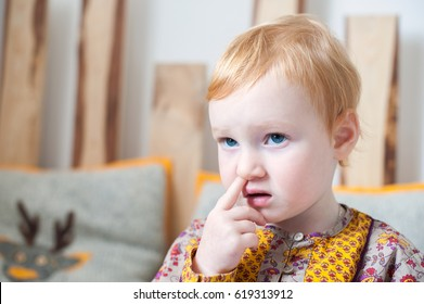 Red-haired girl picking her nose