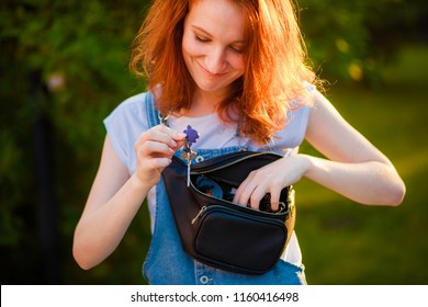Red-haired girl pulls out of her waist bag