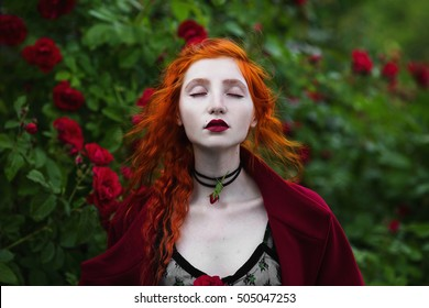 The red-haired girl in red coat posing on a background of a bush with red roses. Red lips and red nails. Ring on a finger. Long hair. Pale skin. Pendant on the neck.