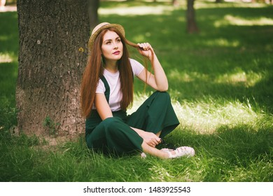 Red-haired girl resting in a park near a tree