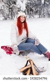 A red-haired girl is roasting marshmallows on an open fire in winter