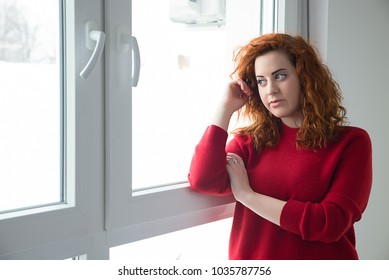 Red-haired girl in the room by the window