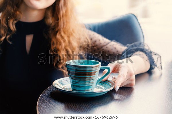 The red-haired girl sits at a table in a cafe and her hand touches a green ceramic cup in the Japanese style. At the girl falls light from the window from behind.