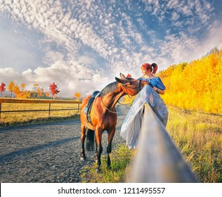 red-haired girl sitting on the fence and stroking the horse