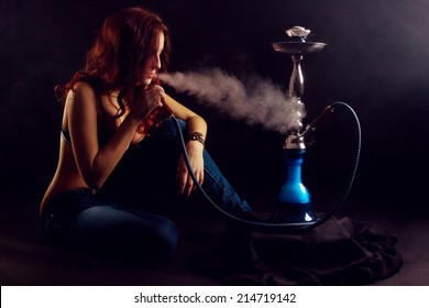 Red-haired girl sitting smoking a hookah. Girl enjoying exhales.