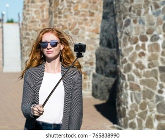 red-haired girl in sunglasses with action camera at a stone wall