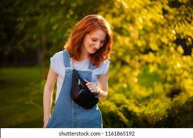 red-haired girl with waist bag in the Park