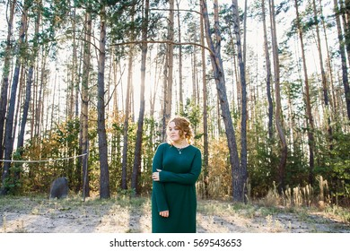 The red-haired girl walking in the woods in the summer